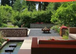 Terrasse mit großformatigen Platten, Kiesfläche und Bambushecke mit Loungemöbeln