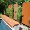 Cortenstahl-Wand als Sichtachse am Ende des Pool mit Bambuspflanzen