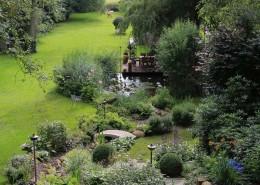 Langer Bachlauf mit Natursteinen und Granitbrücke